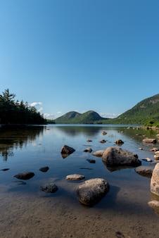 大きな石がある湖の垂直方向のショットとそれに空の反射
