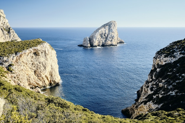 遠くに岩がある海の近くの芝生の崖のハイアングルショット