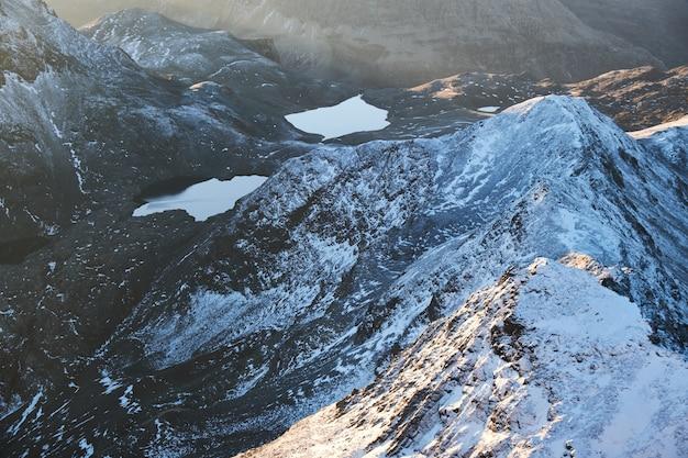 昼間の池の近くの雪に覆われた山の空中ショット