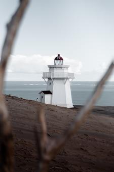Вертикальный селективный выстрел из белого маяка на песчаном берегу моря