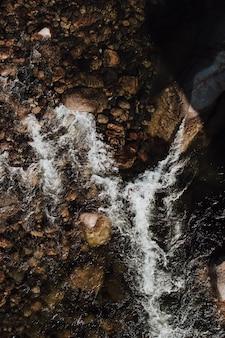 海水の体に岩の垂直の空中ショット