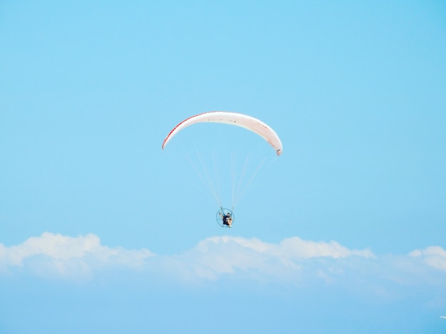 Низкий угол выстрела человека с парашютом вниз под красивым облачным небом