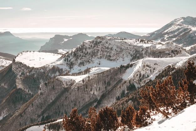 Вид с высоты птичьего полета на заснеженные горы под голубым небом