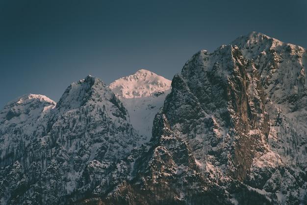 Красивые высокие скалистые горы со снежной горой между ними