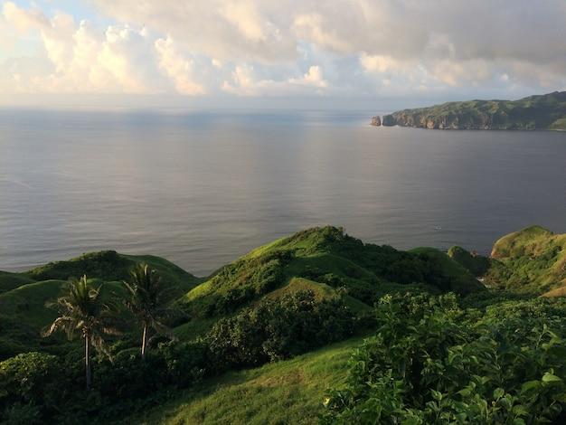 曇り空の下、海に囲まれた緑に覆われた丘