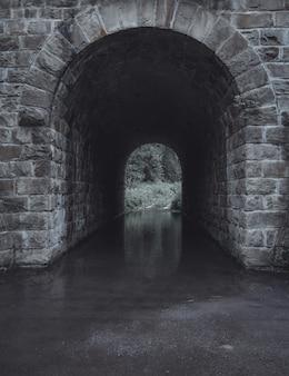 灰色の石造りの水のトンネルの垂直ショット