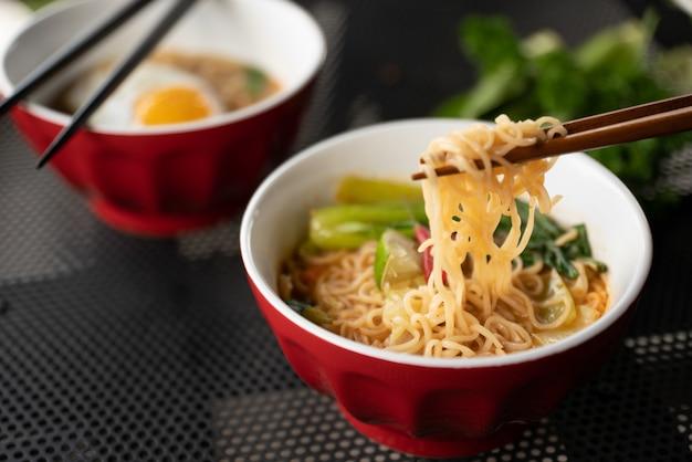 Закрыть выстрел из палочек для еды с лапшой возле супа с размытым фоном