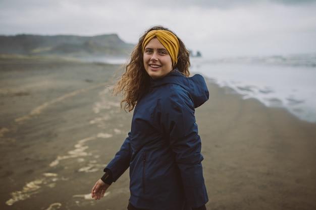 寒い秋の日にビーチの新鮮な空気を楽しむモデルのショット