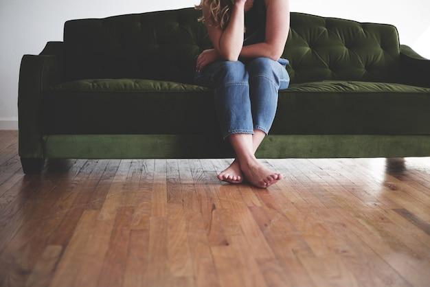 深い思考の緑のソファに座っているブルージーンズに裸足の女性の水平ショット