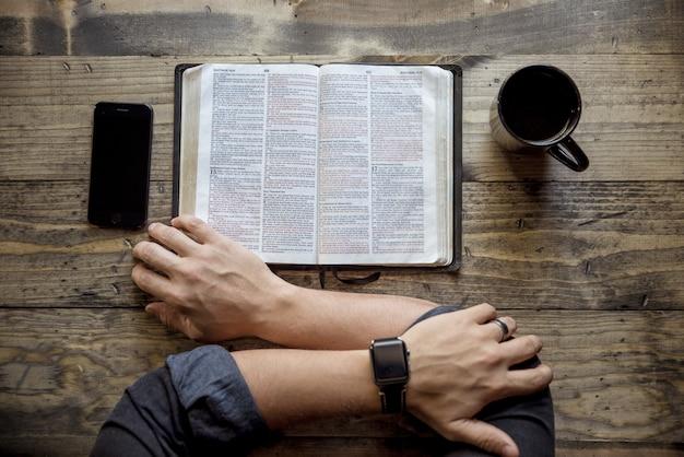 木製のテーブルにコーヒーとスマートフォンの近くの本を読んでいる人のオーバーヘッドショット