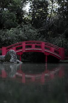 Маленький красный мост, отражающий на воде в лесу, в зелени под солнечным светом