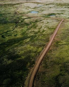 Узкая мутная дорога в зеленом поле снят сверху