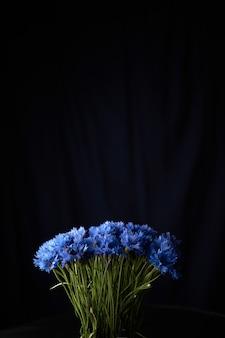 黒の背景に美しい青い花びらのアジサイの花の花束