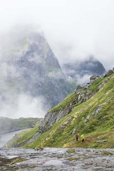 霧深い天候でロフォーテン諸島の山でハイキングする人々