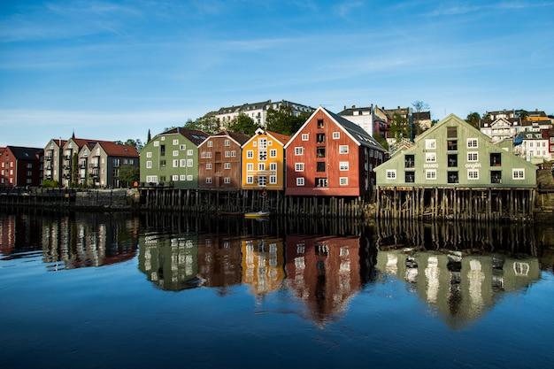 澄んだ青い空の下で湖に映る海岸の建物の範囲