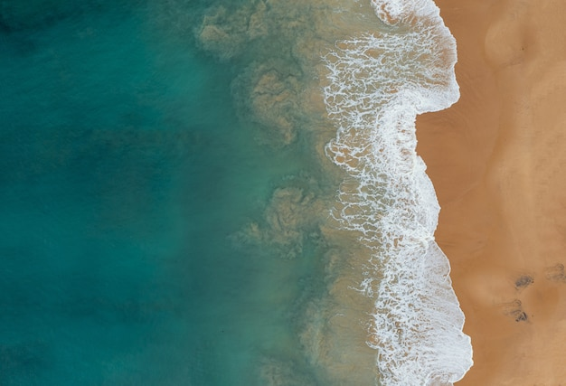 Аэрофотоснимок красивых океанских волн, встречая пески на пляже