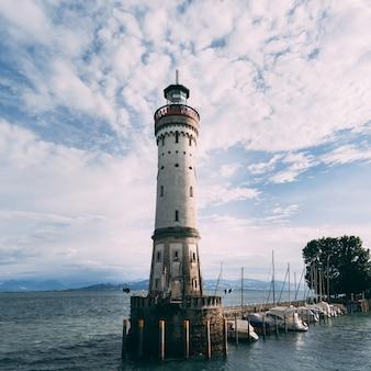 美しい曇り空の下で海の白い灯台の近くの船の低角度のビュー