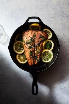 白い表面に黒い鍋にレモンとサーモンのグリル