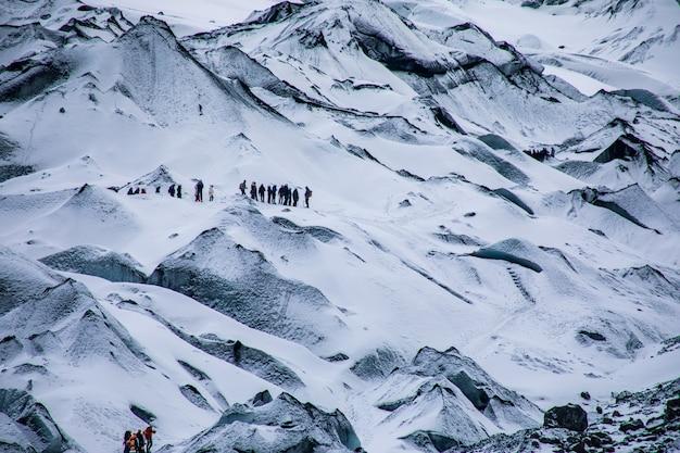 雪に覆われた険しい白い山々とハイキング旅行者