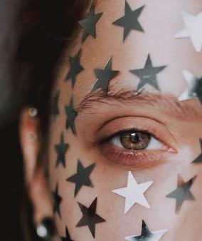 Женский красивый глаз с серебряными звездами на лице