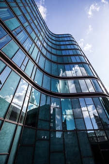 ガラスのファサードに囲まれた高層ビルで、周囲の建物が反射しています