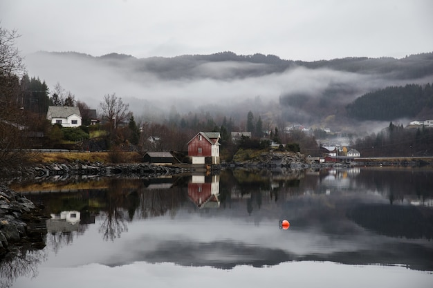 Озеро окружено постройками с покрытыми лесами горами и отражением тумана на воде