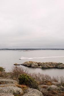 Лодка плывет по морю под пасмурным небом