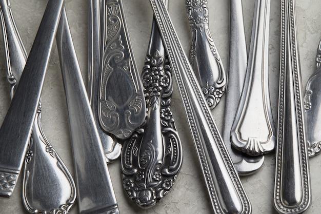 Много серебряных вилок и ложек с античными узорами на белой поверхности