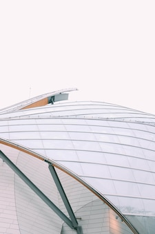 灰色の空の下で白いガラス窓のあるモダンな建物のクローズアップの外観
