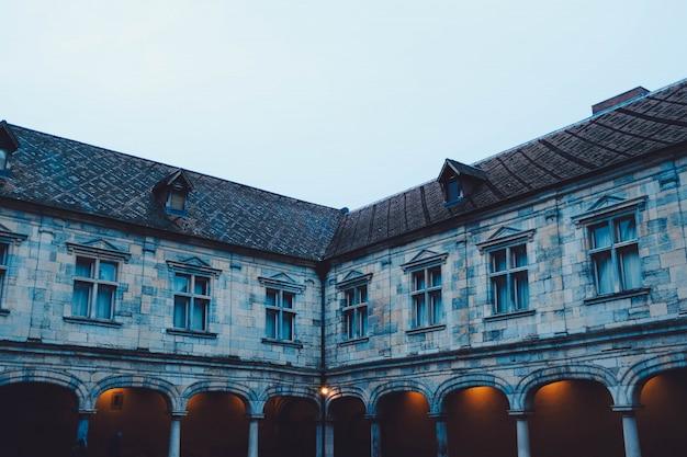 昼間に青空の下でライトが点灯する古い古代の建物の隅