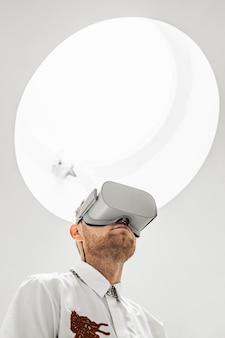 Вертикальный низкий угол съемки человека, носящего очки виртуальной реальности под белым светом