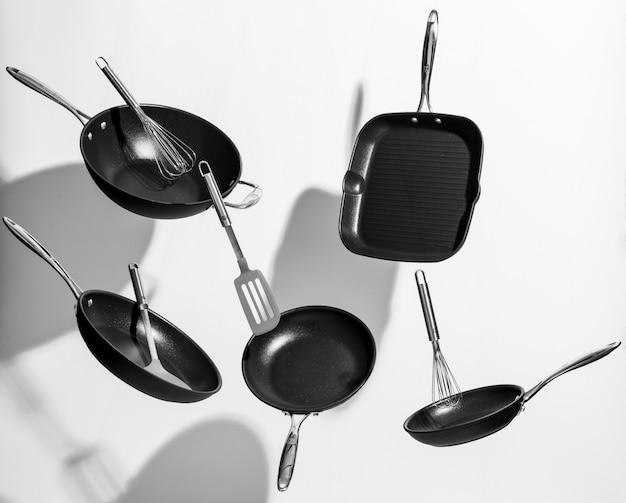 Интересный снимок модной черной кухонной утвари, танцующей на белом фоне