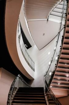 Вертикальная съемка бетонной лестницы внутри здания с включенным освещением
