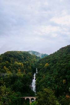 Водопад течет посреди захватывающих зеленых пейзажей
