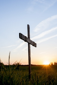 青い空に輝く太陽と芝生のフィールドで木製の十字架