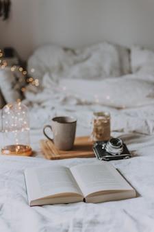 開いた本、カメラ、トレイ、白いシーツ付きのベッドの上のマグカップ