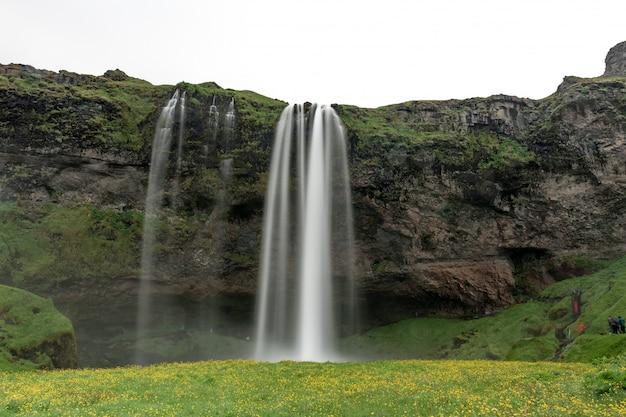 Выстрел из водопада течет по скале посреди зеленого пейзажа