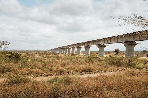 ケニアのナイロビで撮影された曇り空の下の砂漠にかかる長い橋
