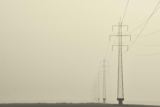 通りの真ん中にある送電鉄塔の霧のショット