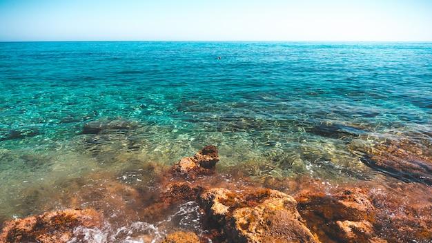Прекрасный вид на чистый синий океан, снятый с берега в греции