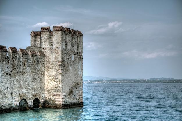 Красивая съемка старинного исторического здания в океане в сирмионе, италия
