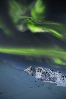 Вертикальный выстрел из заснеженных гор под красивым северным сиянием в небе