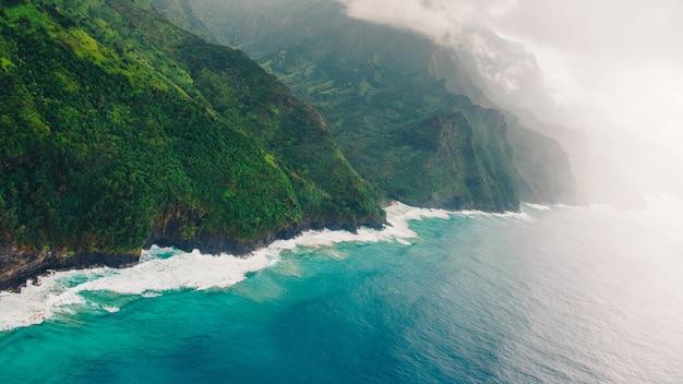 ハワイ、カウアイで撮影された穏やかな青い海の上の美しい霧の崖のハイアングルショット