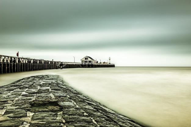 息をのむような空の下で海の近くの桟橋の美しいショット