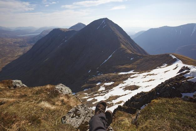 山の頂上で地面に座っている人間の脚のハイアングルショット