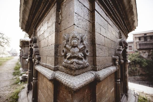 ネパールのヒンドゥー教寺院で彫刻をした壁のクローズアップショット