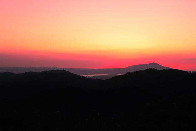息をのむような夕焼け空の下の高い芝生の丘の美しい風景
