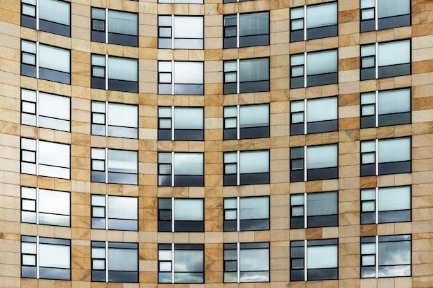 創造的な形の窓があるモダンな茶色の建物のローアングルショット