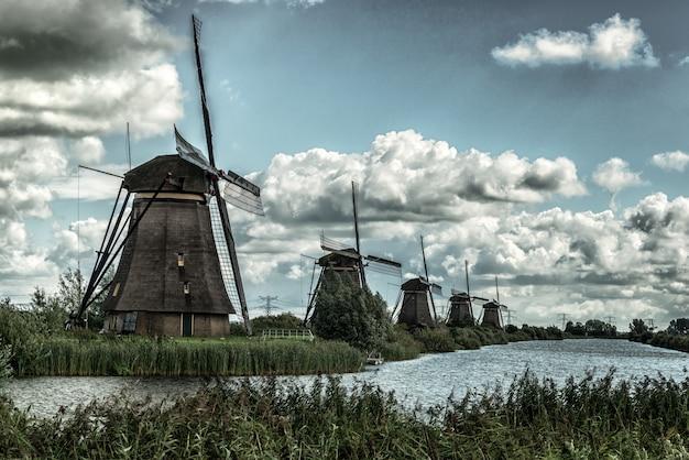 息をのむような曇り空の下で湖に反映される風車の美しいショット