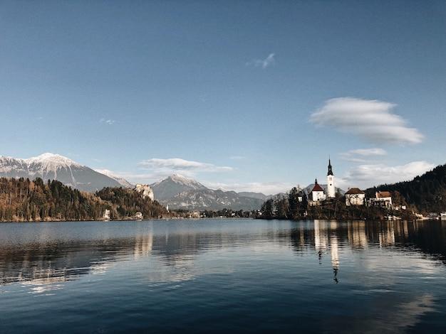 Древний замок в окружении горных пейзажей, отражающихся в озере